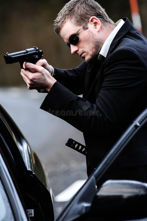 El hombre tira de un arma en coche fotos de archivo libres de regalías