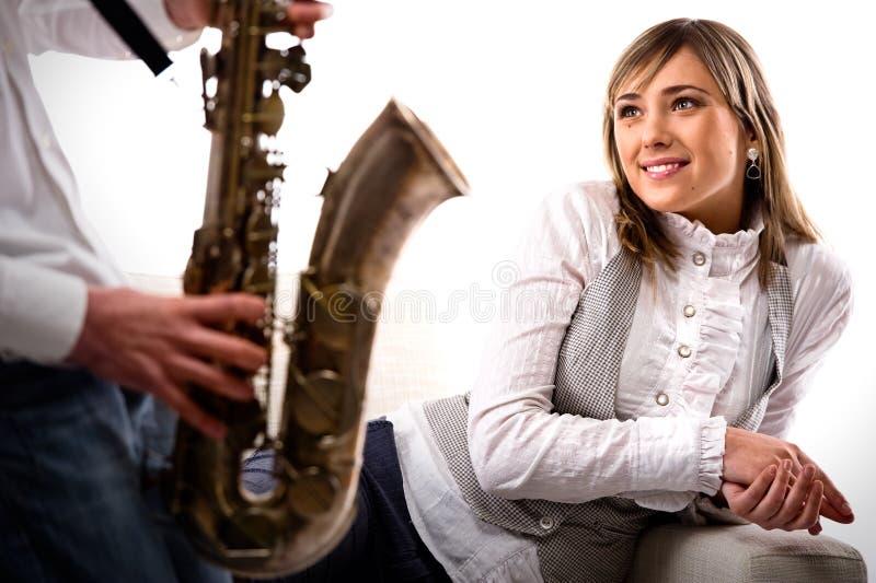 El hombre toca el saxofón para la muchacha imagen de archivo