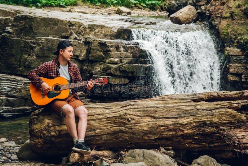 El hombre toca una guitarra que se sienta en un tronco de un árbol contra una cascada Espacio para su mensaje de texto o contenid fotos de archivo libres de regalías