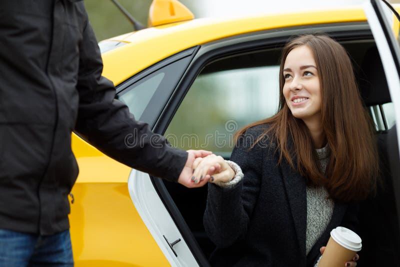 El hombre toma la mano de la mujer para ayudar a salir del taxi imagen de archivo