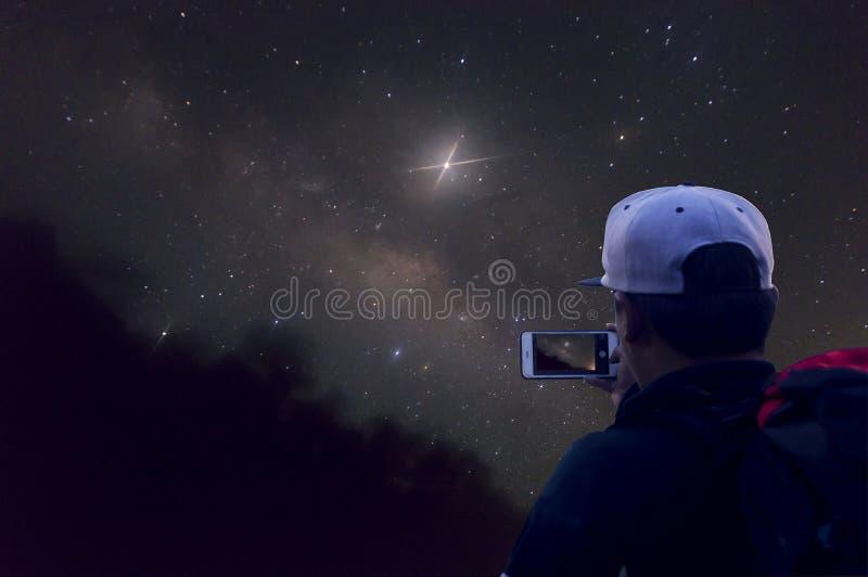 El hombre toma una foto, una galaxia de la vía láctea, campos de arroz de arroz y montañas Fotograf?a larga de la exposici?n imágenes de archivo libres de regalías