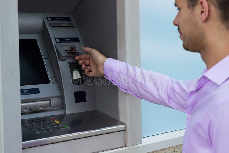 El hombre toma una tarjeta de crédito de una atmósfera foto de archivo libre de regalías