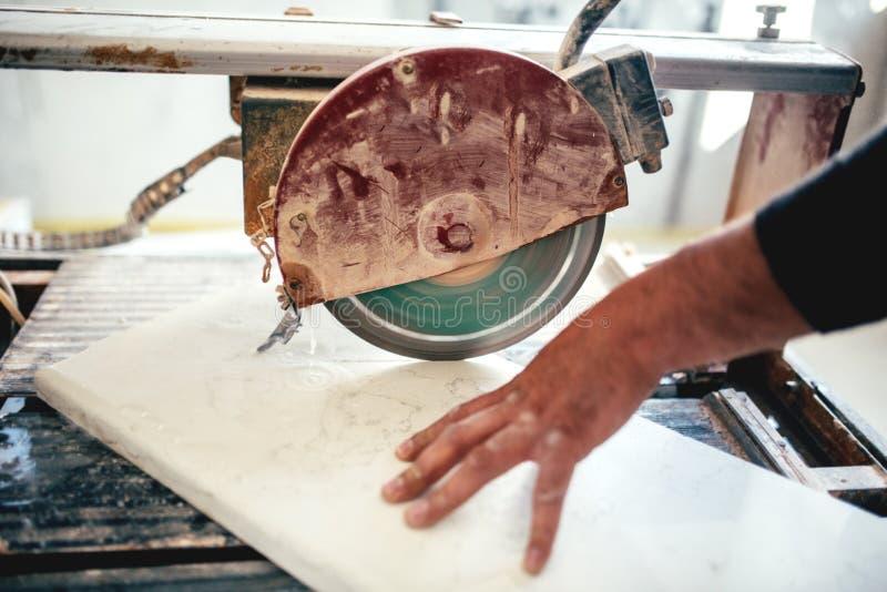 el hombre, trabajador que usaba la circular vio para cortar la pizarra y el mármol foto de archivo
