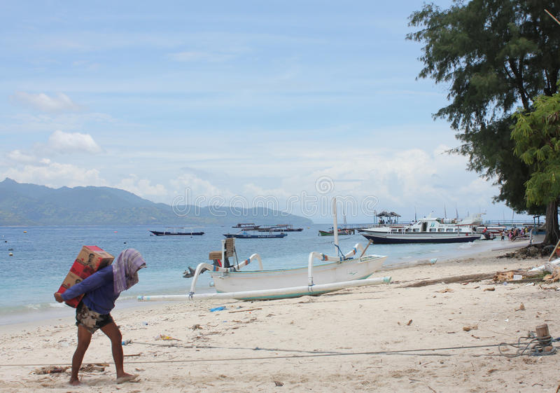 El hombre trae el suministro de alimentos a la isla foto de archivo