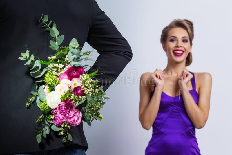 El hombre trae las flores a la mujer imagen de archivo