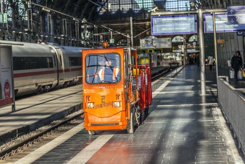 El hombre transporta mercancías en un coche eléctrico en el ferrocarril fotografía de archivo