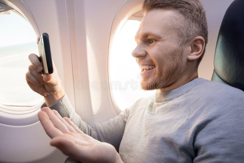 El hombre turístico del viajero está mirando el vídeo en el teléfono en avión imagen de archivo libre de regalías