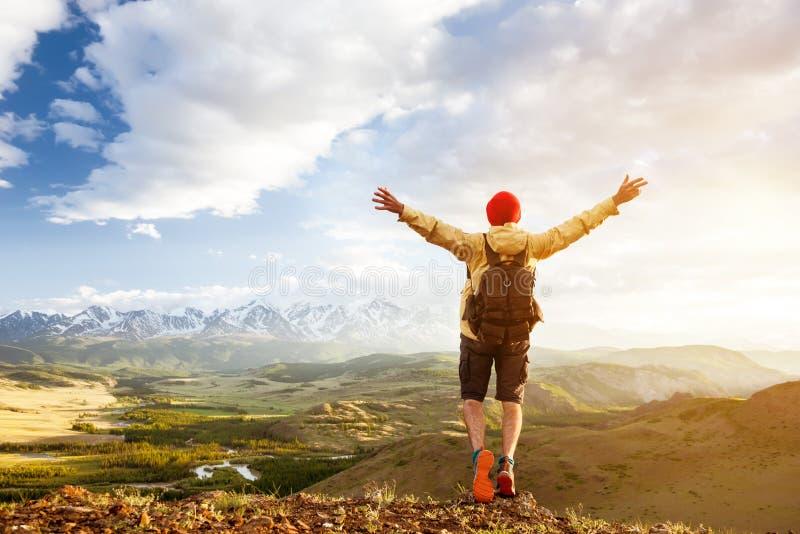 El hombre turístico feliz aumentó los brazos contra las montañas de la puesta del sol imagenes de archivo
