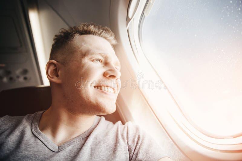 El hombre turístico feliz hace la foto del selfie en aeroplano de los aviones de la cabina antes de salida concepto del recorrido imagenes de archivo