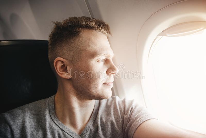 El hombre turístico feliz hace la foto del selfie en aeroplano de los aviones de la cabina antes de salida concepto del recorrido imagen de archivo libre de regalías
