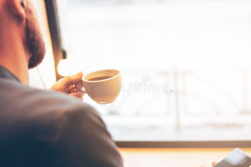 El hombre usando el tel?fono m?vil, sent?ndose con caf? en el caf? Reflexión de la luz del sol en fondo foto de archivo
