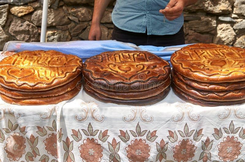 El hombre vende el pan armenio tradicional con escrituras en el mercado al aire libre imagen de archivo libre de regalías