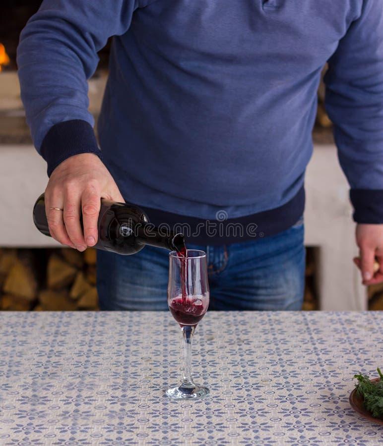 El hombre vierte un vino rojo en un vidrio contra la llama ardiente de la chimenea imagenes de archivo