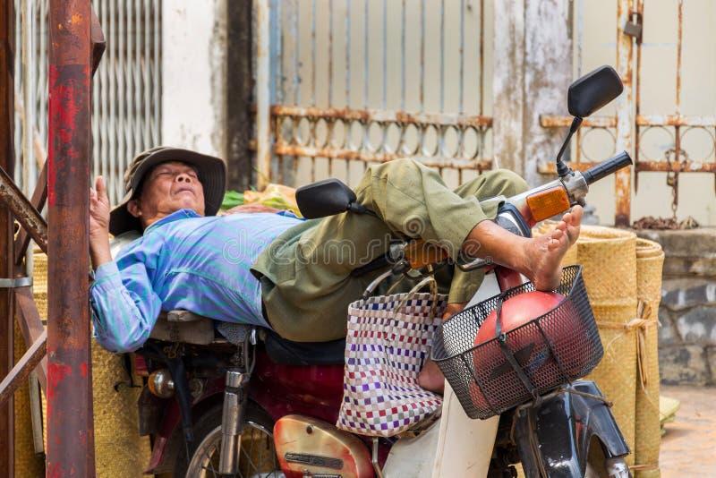 El hombre vietnamita duerme en la moto en la calle en mi Tho, Vietnam fotos de archivo libres de regalías