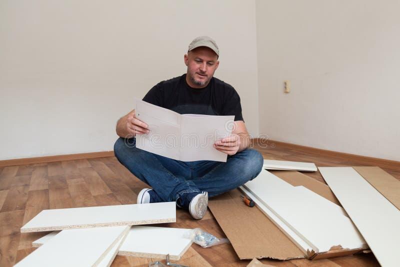 El hombre vistió los muebles de junta casuales en nueva casa Reparación del carpintero y muebles de junta en casa imagen de archivo