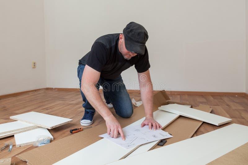 El hombre visti? los muebles de junta casuales en nueva casa Reparaci?n del carpintero y muebles de junta en casa fotos de archivo libres de regalías