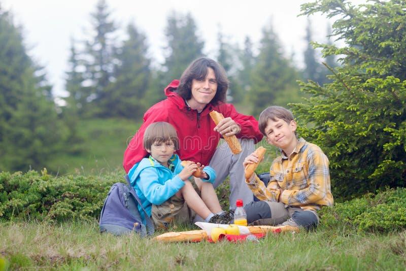 El hombre y dos muchachos tienen comida campestre en foresr fotografía de archivo
