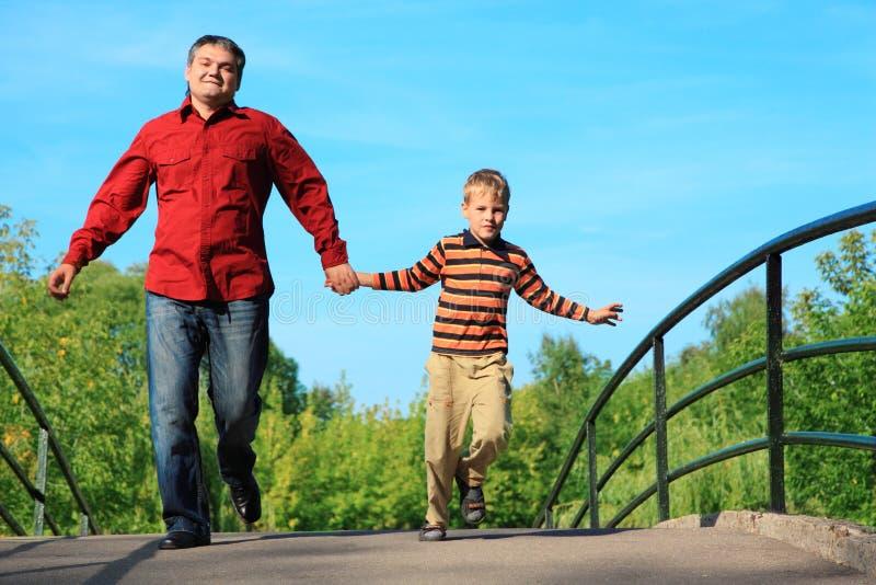 El hombre y el muchacho se ejecutan en el puente en verano imagen de archivo