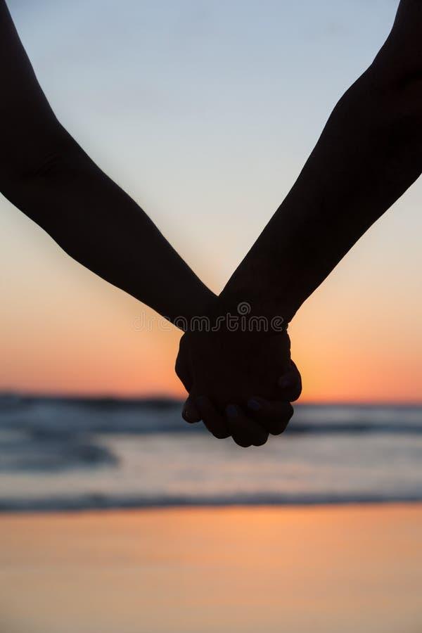 Pares jovenes que llevan a cabo las manos en la playa del mar en la puesta del sol imagenes de archivo