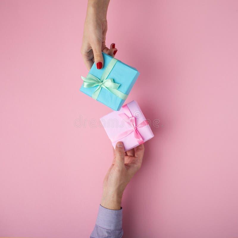 El hombre y la muchacha que intercambiaban los regalos de mano a mano, cajas envolvieron en papel decorativo con un arco en fondo fotografía de archivo libre de regalías