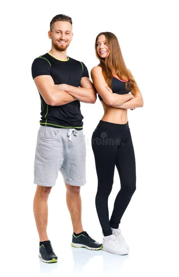 El hombre y la mujer atléticos después de la aptitud ejercitan en el blanco fotos de archivo