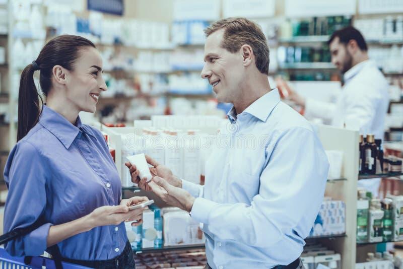 El hombre y la mujer compra medicamentos en farmacia foto de archivo libre de regalías