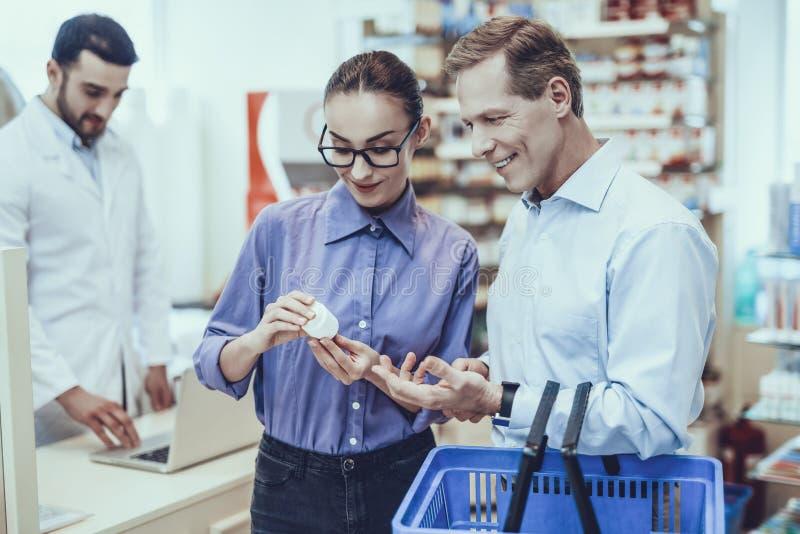 El hombre y la mujer compra medicamentos en farmacia imagenes de archivo