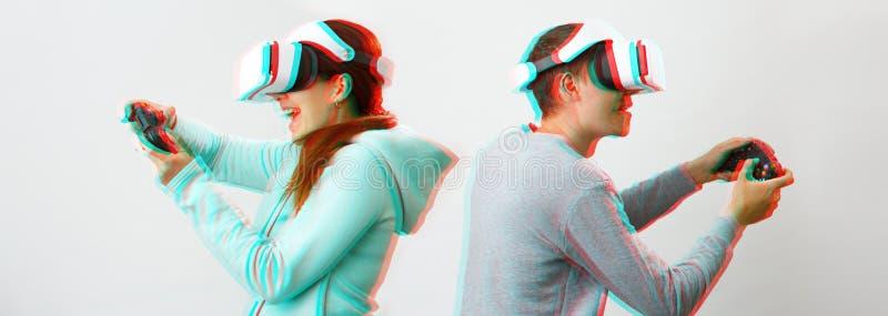 El hombre y la mujer con las auriculares de la realidad virtual est?n jugando al juego Imagen con efecto de la interferencia foto de archivo libre de regalías