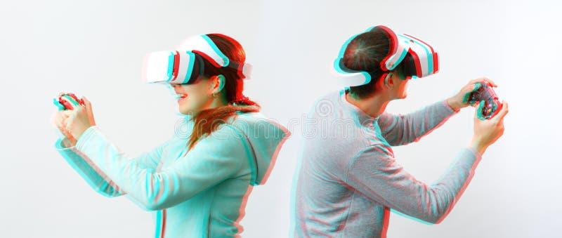 El hombre y la mujer con las auriculares de la realidad virtual est?n jugando al juego Imagen con efecto de la interferencia imagen de archivo