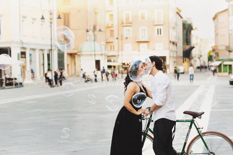 El hombre y la mujer con una bicicleta se están besando en la ciudad vieja Alrededor de ellos son las burbujas del agua Historia  imagenes de archivo