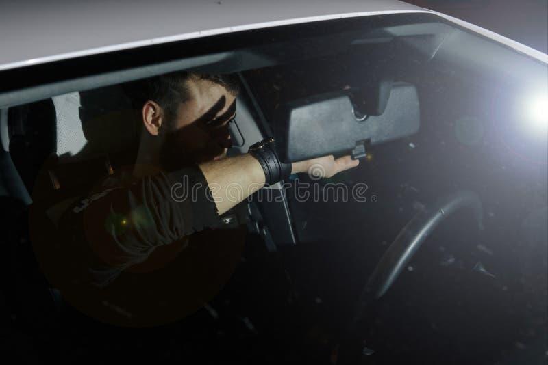 El hombre y la mujer conducen un coche en la situación de emergencia Noche de la tarde imagen de archivo libre de regalías
