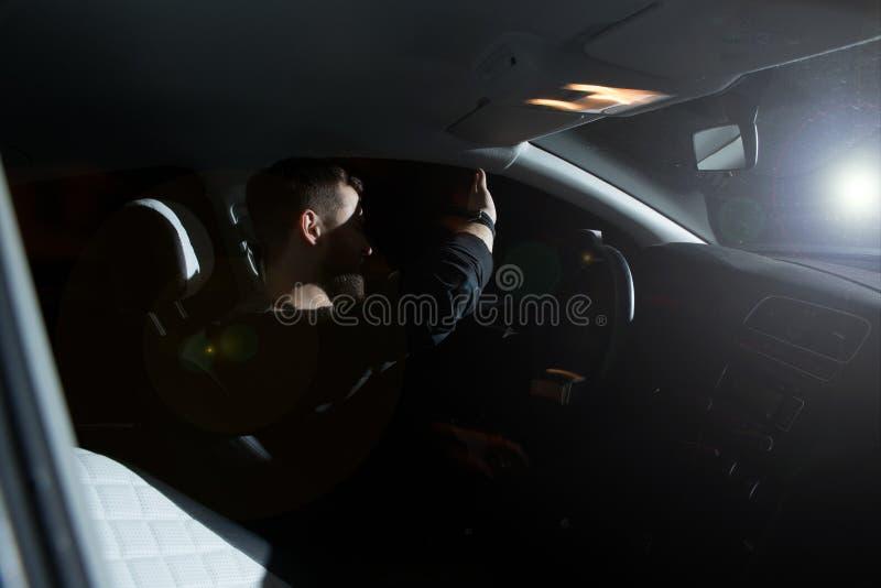 El hombre y la mujer conducen un coche en la situación de emergencia Noche de la tarde foto de archivo libre de regalías