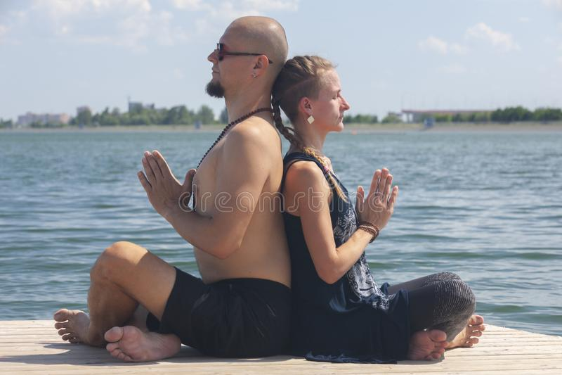 El hombre y la mujer embarazada est?n haciendo yoga en la playa imágenes de archivo libres de regalías