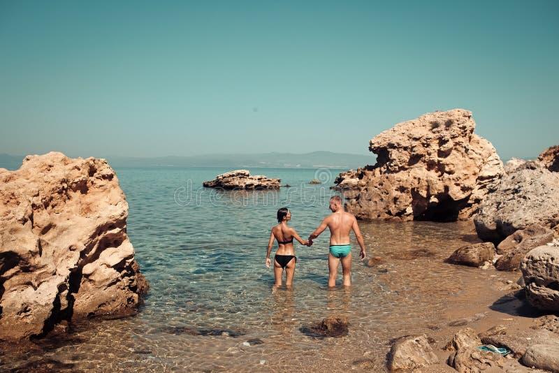 El hombre y la mujer en bikini se coloca en el mar entre el filón el día soleado El par en amor se coloca en agua cerca de piedra imagenes de archivo