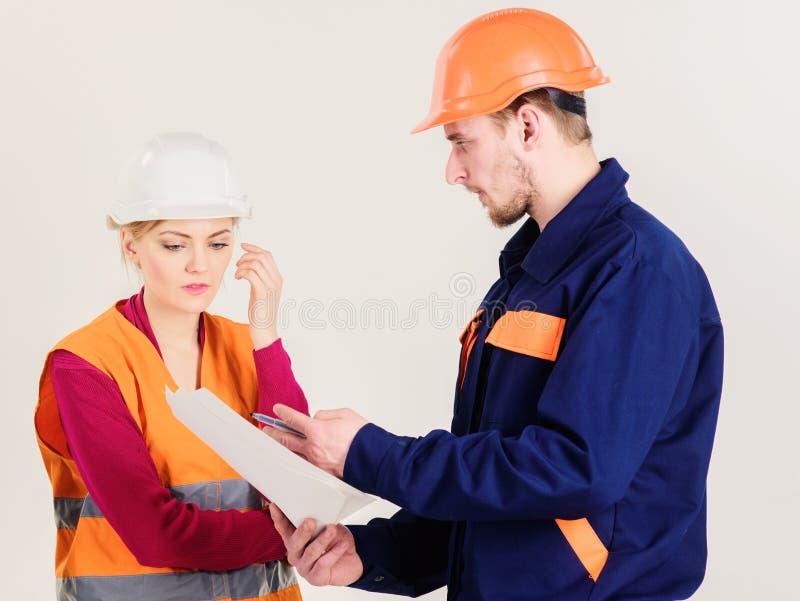 El hombre y la mujer en cascos, uniforme mira el modelo fotografía de archivo