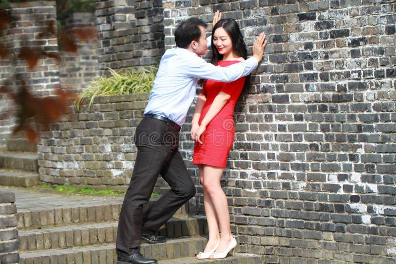 El hombre y la mujer en el vestido rojo se colocan en la pared de Ming Dynasty foto de archivo