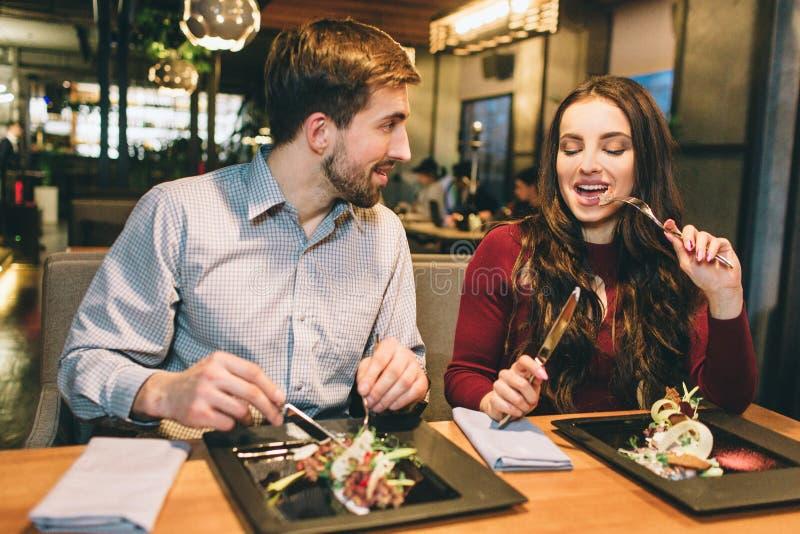 El hombre y la mujer están comiendo en la tabla en restaurante y están hablando el uno al otro Están disfrutando de la compañía d imagenes de archivo
