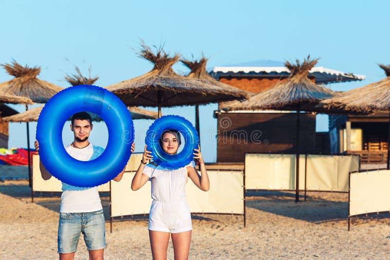 El hombre y la mujer están presentando en la playa y están llevando a cabo círculos inflables concepto de día de fiesta del mar d foto de archivo libre de regalías