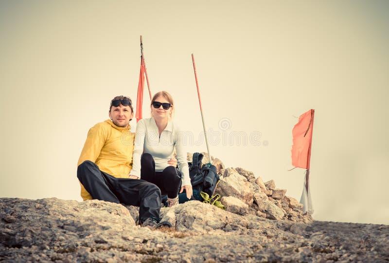 El hombre y la mujer juntan a viajeros en cumbre de la montaña fotografía de archivo libre de regalías