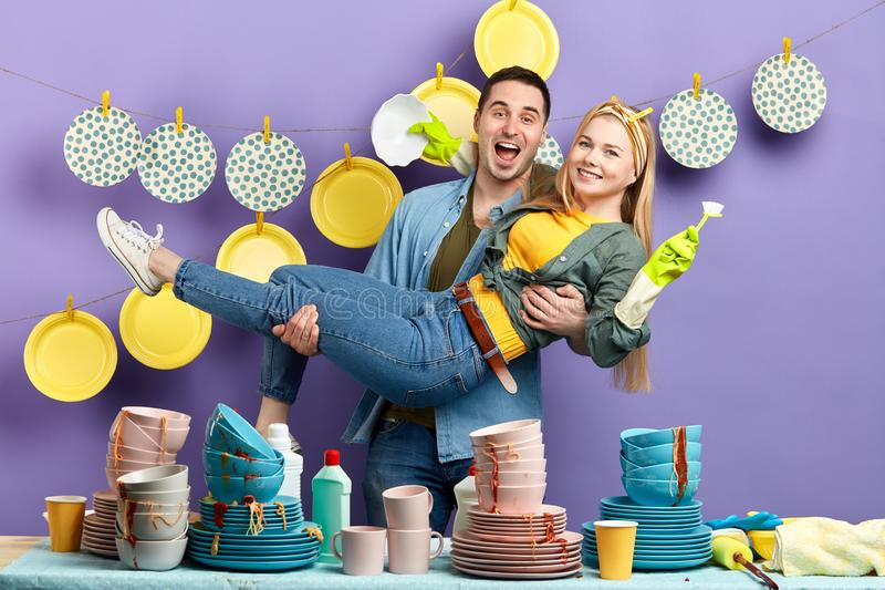 El hombre y la mujer locos consiguen placer de platos que se lavan imagenes de archivo