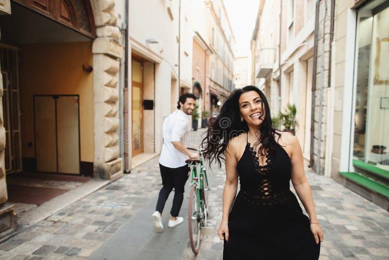 El hombre y la mujer maravillosamente vestidos están caminando en la ciudad vieja con una bicicleta Historia de amor en Rímini, I imagen de archivo