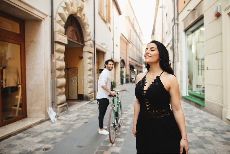 El hombre y la mujer maravillosamente vestidos están caminando en la ciudad vieja con una bicicleta Historia de amor en Rímini, I foto de archivo libre de regalías