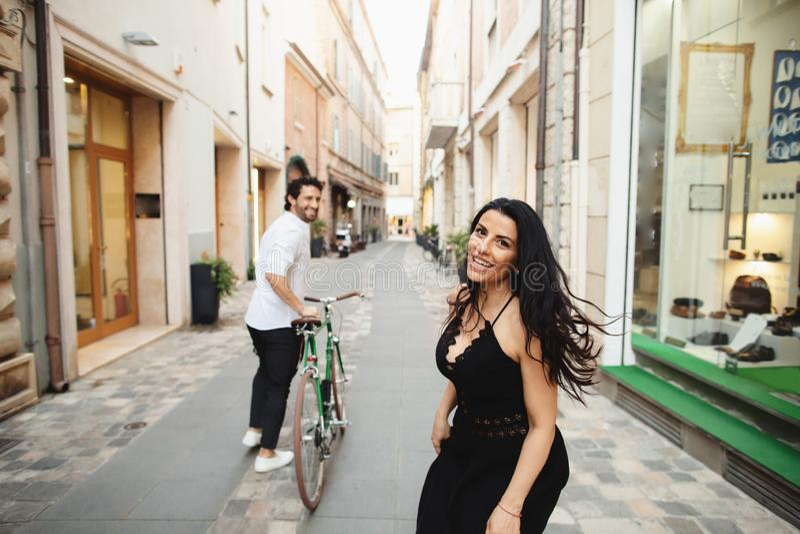El hombre y la mujer maravillosamente vestidos están caminando en la ciudad vieja con una bicicleta Historia de amor en Rímini, I fotos de archivo libres de regalías