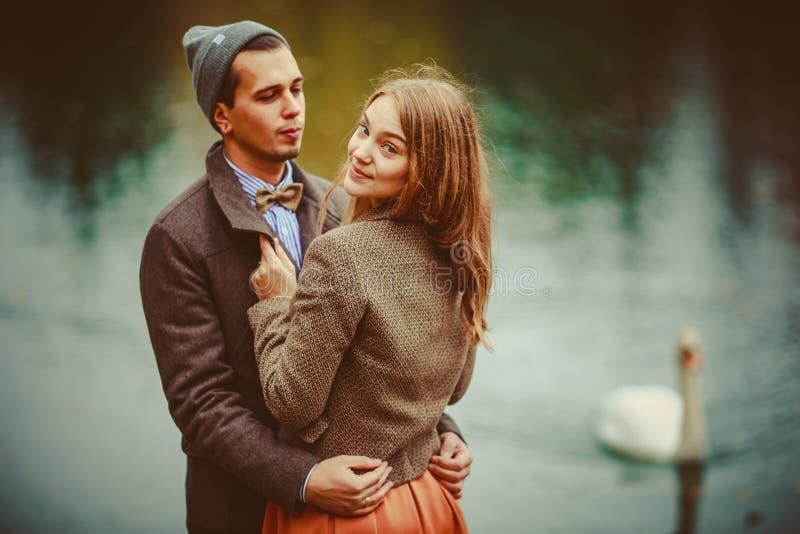 El hombre y la mujer que abrazan cerca del lago imagen de archivo
