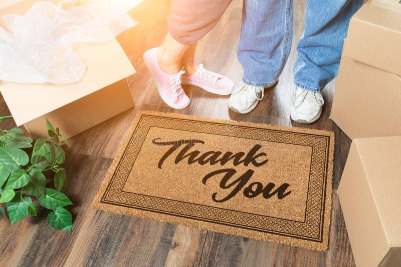 El hombre y la mujer que desempaquetan cerca le agradecen Doo Mat, las cajas de mudanza y planta fotos de archivo libres de regalías