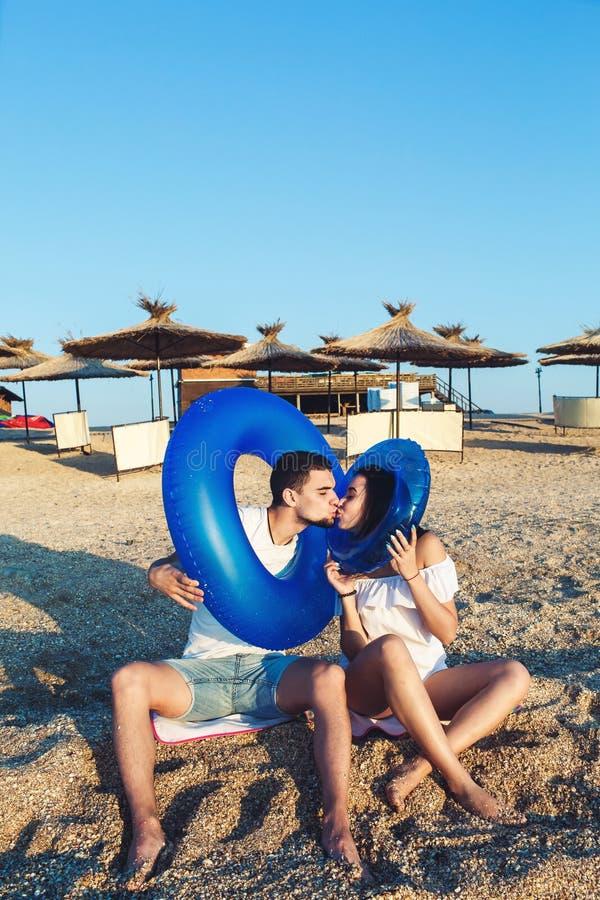 El hombre y la mujer se están sentando en la playa y están llevando a cabo círculos inflables concepto de día de fiesta del mar d foto de archivo libre de regalías
