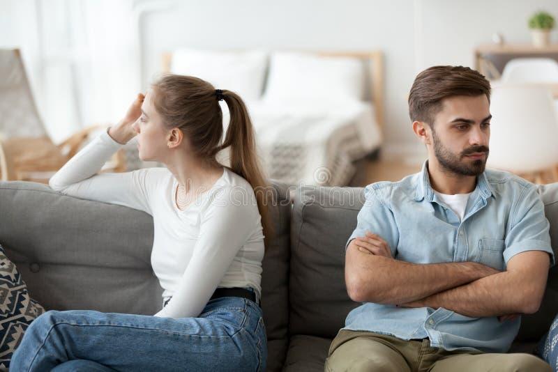 El hombre y la mujer se sientan por separado en el sofá después de lucha imágenes de archivo libres de regalías