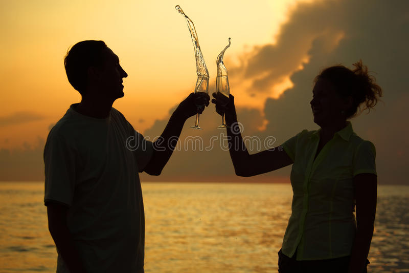 El hombre y la mujer tintinean los vidrios. Salpica del vino.
