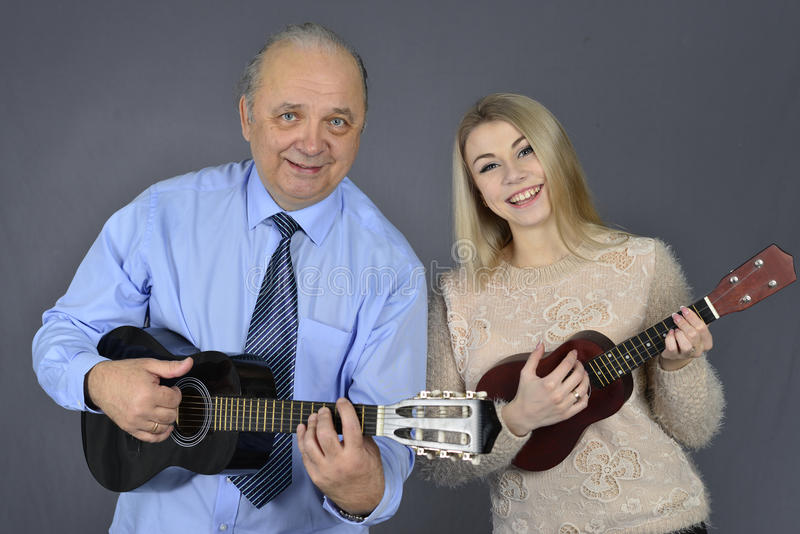 El hombre y la mujer tocan la guitarra fotografía de archivo libre de regalías