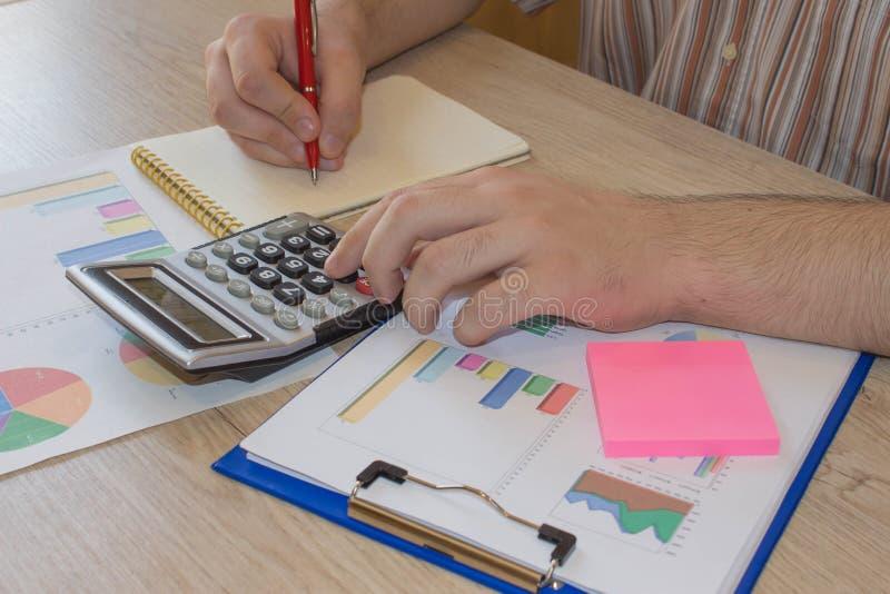El hombre y el ordenador están utilizando una calculadora en la tabla en el cuarto de la oficina Concepto de la contabilidad y de foto de archivo